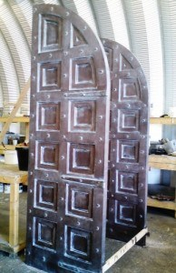 Hardwood arched top, paneled double doors painted and dressed.