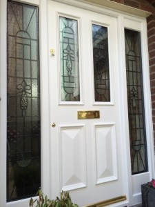 Painted hardwood, four panel entrance door with matching frame and double glazed leaded glass lights