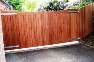 View of Sapele timber driveway gates showing matching sapele fence panel in Co Down
