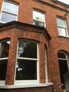 Replacement, painted hardwood, double glazed sash windows with curved tops to match the brickwork in Belfast