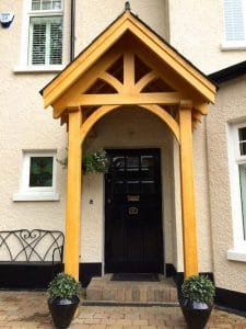 Bespoke, made to measure, light oak coloured, hardwood porch with a traditional slate roof in North Belfast